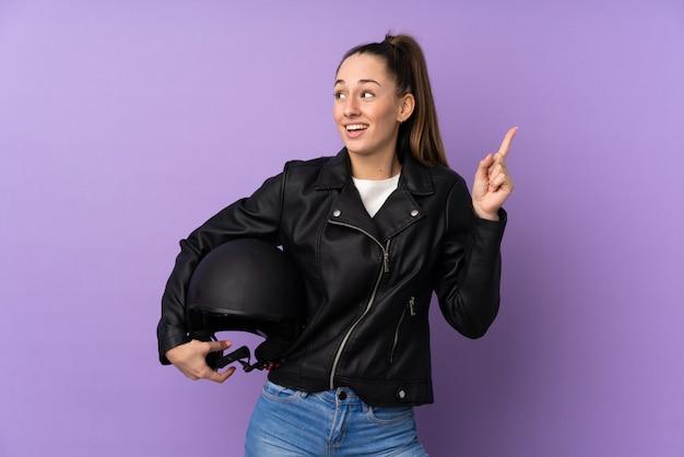 指を持ち上げながら解決策を実現するつもりの分離の紫色の壁の上のオートバイのヘルメットを持つ若いブルネットの女性