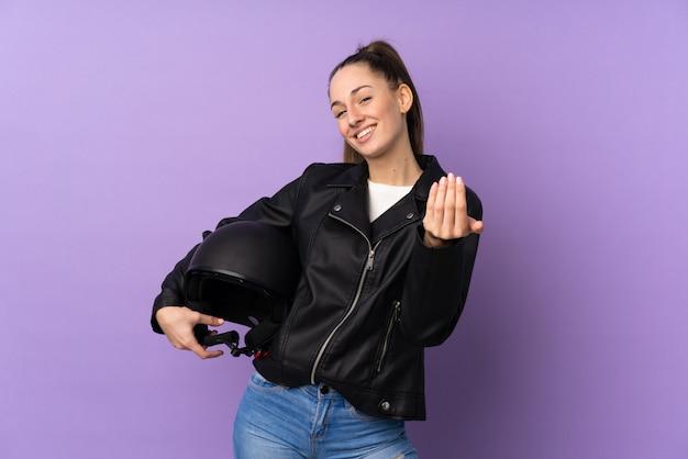 手で来ることを招待して孤立した紫色の壁にオートバイのヘルメットを持つ若いブルネットの女性。あなたが来て幸せ