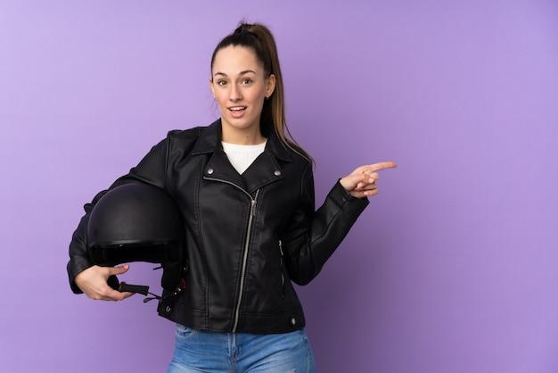 驚いたと側に指を指している分離の紫色の壁の上のオートバイのヘルメットを持つ若いブルネットの女性