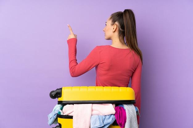 Путешественник женщина с чемоданом, полным одежды над изолированные фиолетовые стены, указывая назад с указательным пальцем