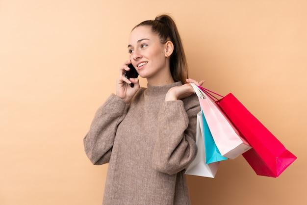 買い物袋を保持していると彼女の携帯電話で友人を呼び出す孤立した壁の上の若いブルネットの女性