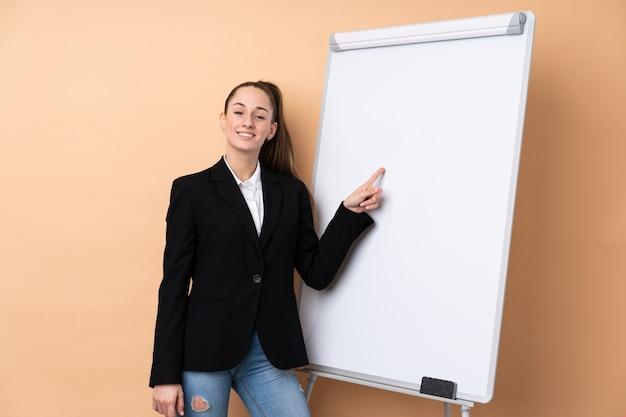 Молодая бизнес-леди над изолированной стеной давая представление на белой доске