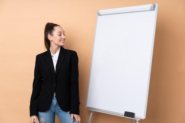 ホワイトボードとプレゼンテーション側にプレゼンテーションを行う分離壁の上の若いビジネス女性