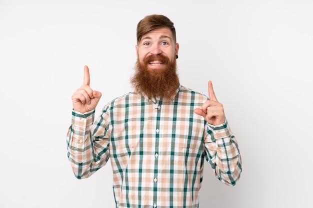 素晴らしいアイデアを指している分離の白い壁の上の長いひげを持つ赤毛の男