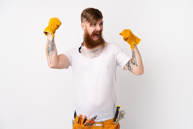 勝利を祝う孤立した白い壁の上の長いひげを持つ赤毛の電気技師男