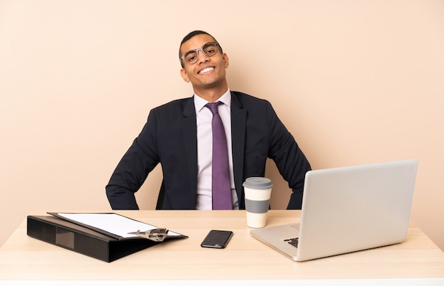 ノートパソコンと腰と笑顔で腕でポーズをとって他のドキュメントと彼のオフィスで若いビジネスマン