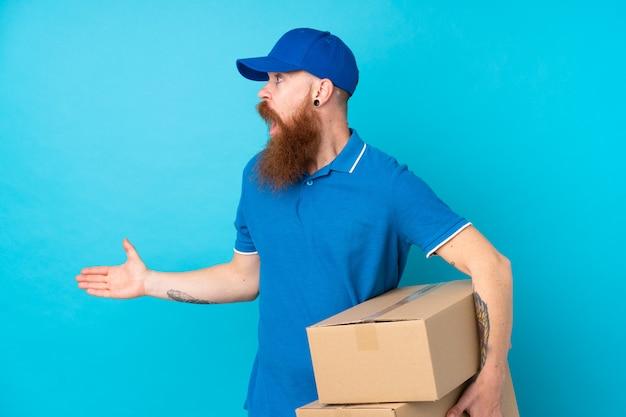 Рыжий доставщик по синей стене с удивленным выражением лица