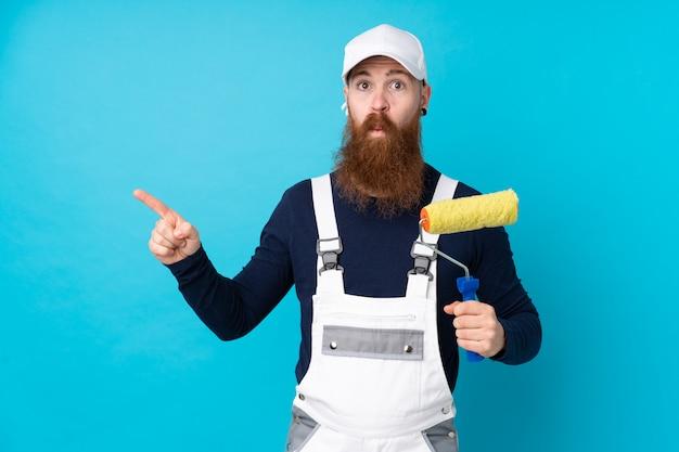 疑いがある側面を指している分離の青い壁の上の長いひげを持つ画家男