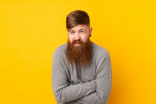 孤立した黄色の壁の凍結上の長いひげを持つ赤毛の男