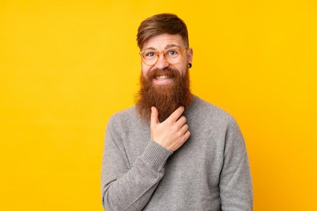 Рыжий мужчина с длинной бородой над изолированной желтой стеной в очках и улыбается