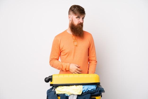 Человек путешественника с чемоданом, полным одежды над изолированной белой стеной, стоящей и смотрящей в сторону