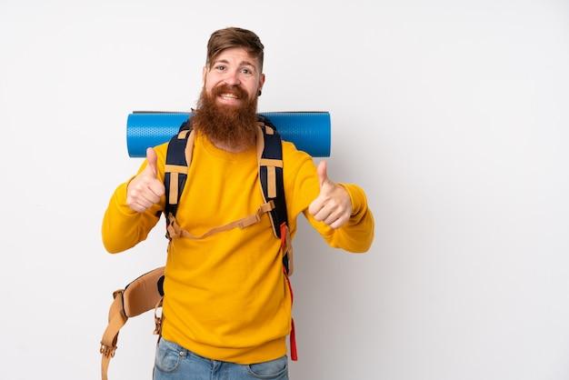 親指ジェスチャーを与える分離の白い壁に大きなバックパックを持つ若い登山家男