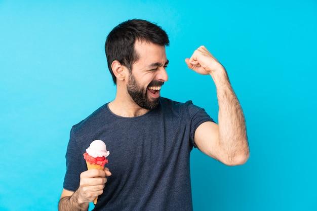 勝利を祝う分離の青い壁の上のコルネットアイスクリームと若い男