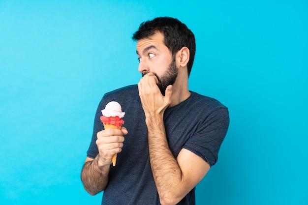 孤立した青い壁の上のコルネットアイスクリームと若い男神経と怖がって口に手を入れて