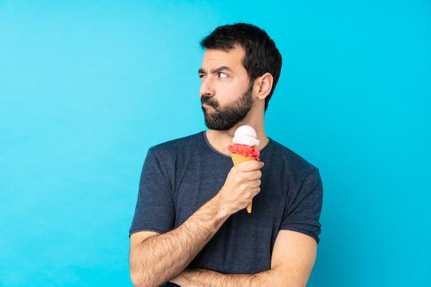 孤立した青い壁の肖像画の上のコルネットアイスクリームと若い男