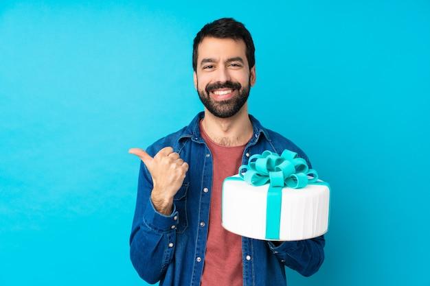 ジェスチャーと笑みを浮かべて親指で孤立した青い壁に大きなケーキを持つ若いハンサムな男