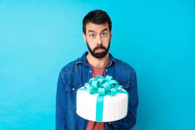 悲しげで落ち込んだ表情で孤立した青い壁の上の大きなケーキで若いハンサムな男