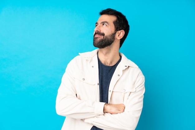 笑みを浮かべて見上げる孤立した青い壁に白いコーデュロイジャケットと若いハンサムな男