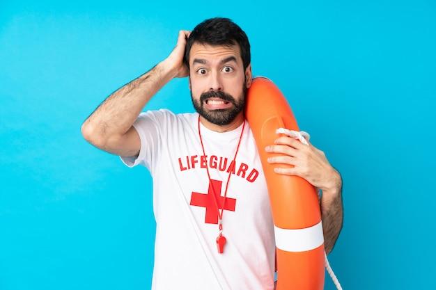 Спасатель человек над изолированной синей стеной расстроен и берет руки на голову