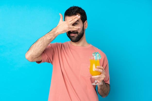 若い男の手で目を覆っていると笑みを浮かべて分離の青い壁にカクテルをかざす