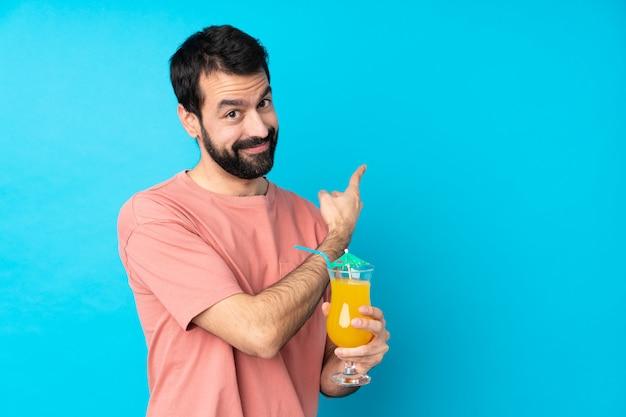 若い男が戻って指している分離の青い壁にカクテルをかざす