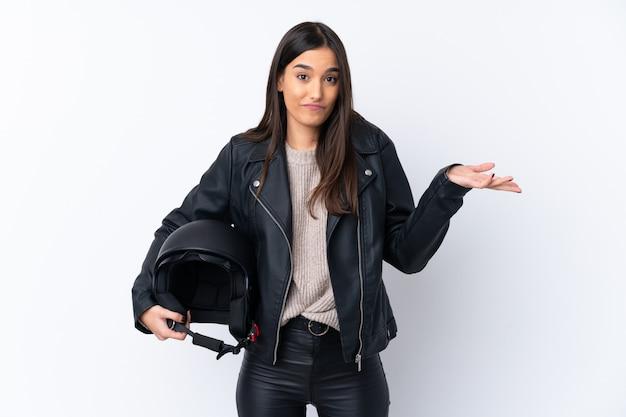 肩を持ち上げながら疑問ジェスチャーを作る分離の白い壁の上のオートバイのヘルメットを持つ若いブルネットの女性