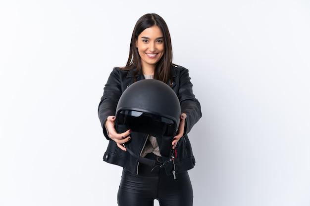 幸せな表情で孤立した白い壁にオートバイのヘルメットを持つ若いブルネットの女性
