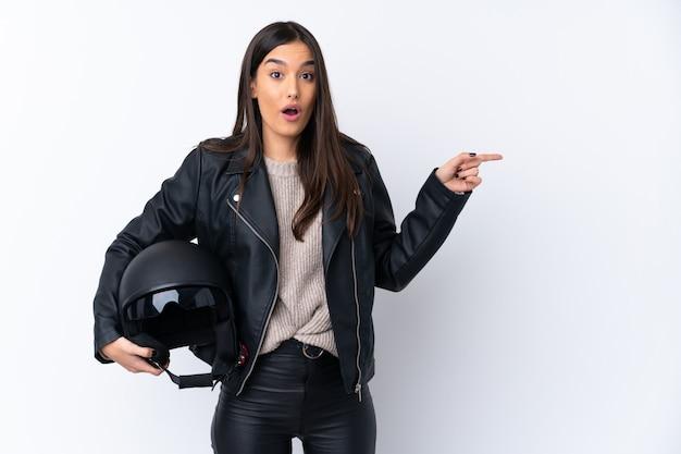 驚いたと指している側の分離の白い壁の上のオートバイのヘルメットを持つ若いブルネットの女性