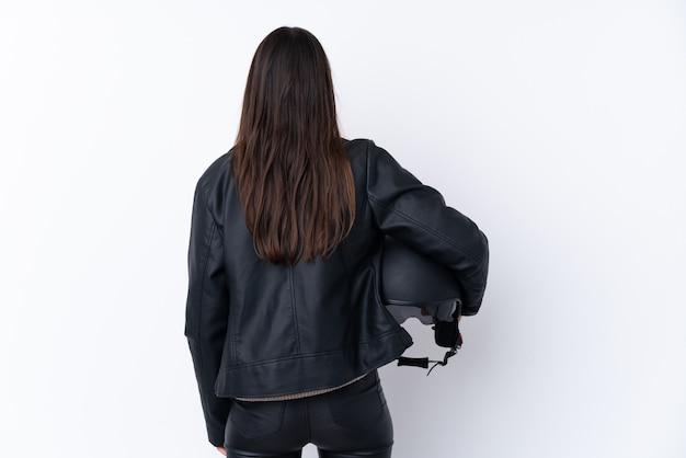 後ろの位置で孤立した白い壁の上のオートバイのヘルメットを持つ若いブルネットの女性