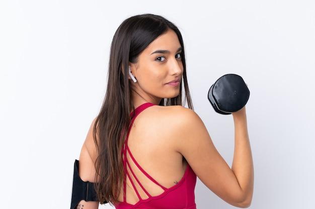 重量挙げを作る分離の白い壁の上の若いスポーツブルネットの女性