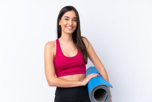 Молодая женщина брюнет спорта над изолированной белой стеной с циновкой и усмехаться
