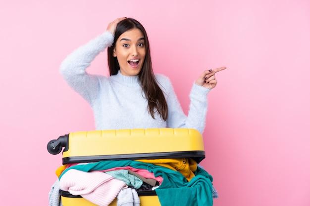 Путешественник женщина с чемоданом, полным одежды над розовой стеной удивлен и указывая пальцем в сторону