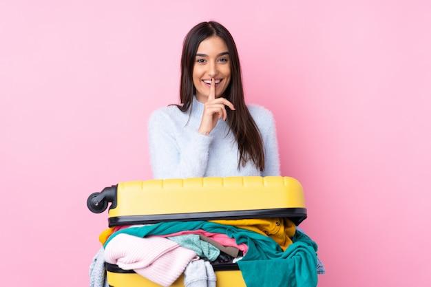 沈黙のジェスチャーをしている孤立したピンクの壁の上の服でいっぱいのスーツケースを持つ旅行者女性