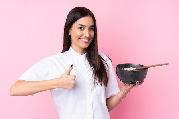 箸で麺のボウルを保持しながら何か良いことが起こったので、親指で孤立したピンクの壁の上の若いブルネットの女性