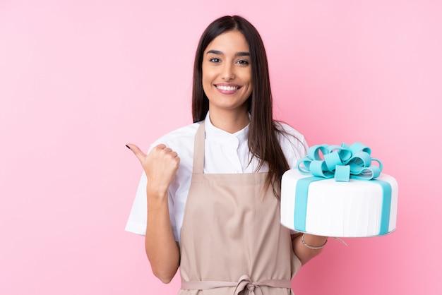 製品を提示する側を指している孤立した壁の上の大きなケーキを持つ若い女性
