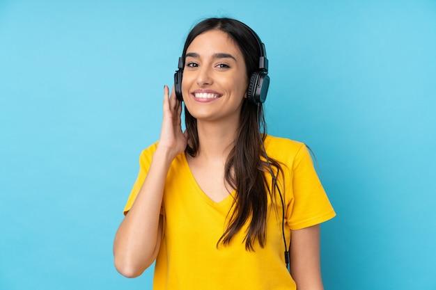 音楽を聴く分離の青い壁の上の若いブルネットの女性