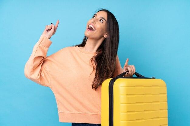 旅行スーツケースと上向きの休暇で孤立した青い壁の上の若いブルネットの女性