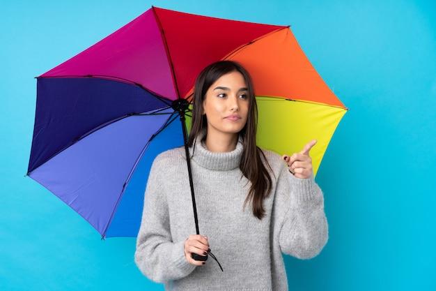 透明なスクリーンに触れる分離の青い壁に傘を置く若いブルネットの女性