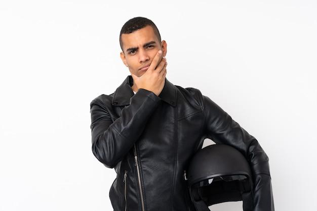 Молодой красивый человек с мотоциклетным шлемом над изолированной белой стеной думая идея