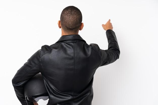 人差し指で戻って指している分離の白い壁にオートバイのヘルメットを持つ若いハンサムな男
