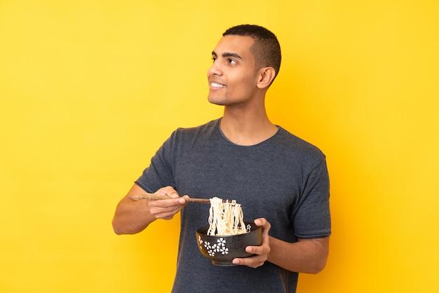 箸で麺のボウルを押しながら見上げる孤立した黄色の壁の上の若いアフリカ系アメリカ人