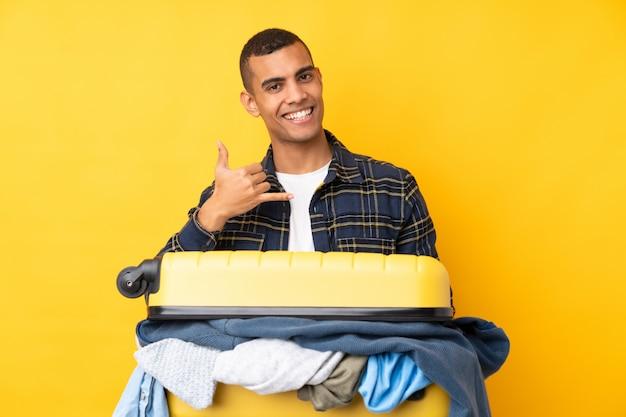 電話ジェスチャーを作る分離の黄色の壁の上の服でいっぱいのスーツケースを持つ旅行者男