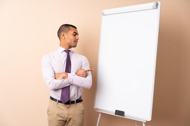 Молодой деловой человек на изолированной стене, давая представление на белой доске и указывая его