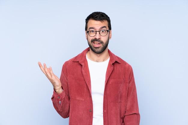 ジェスチャーを疑う青い壁にコーデュロイジャケットを着た若い男