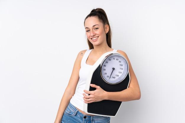 Молодая брюнетка женщина над изолированной белой стеной с весами