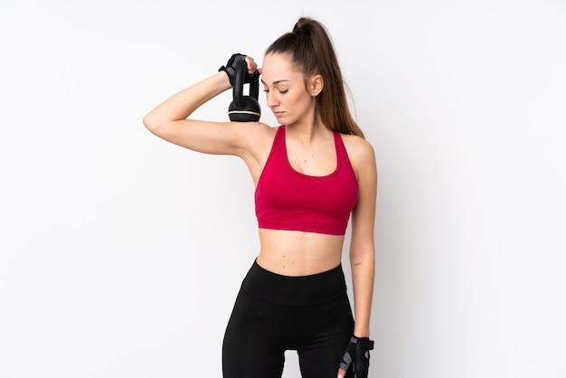 ケトルベルで重量挙げを作る分離の白い壁の上の若いスポーツブルネットの女性
