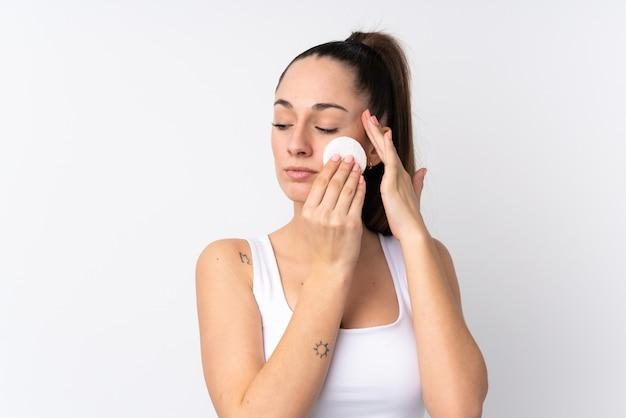 Молодая брюнетка женщина над белой стеной с ватным тампоном для снятия макияжа с ее лица