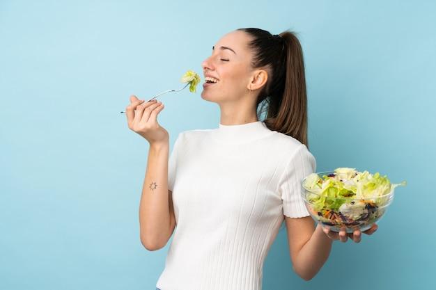 孤立した青い壁にサラダを置く若いブルネットの女性