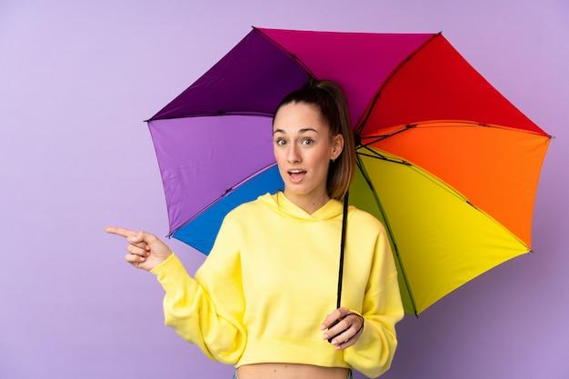 驚いたと側に指を指している分離の紫色の壁に傘を保持している若いブルネットの女性