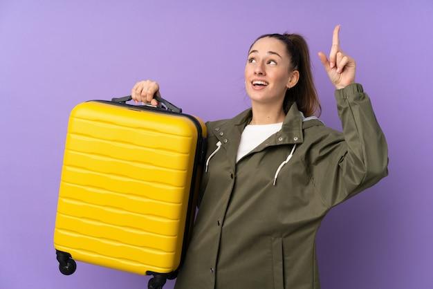 旅行スーツケースと上向きの休暇で孤立した紫色の壁の上の若いブルネットの女性